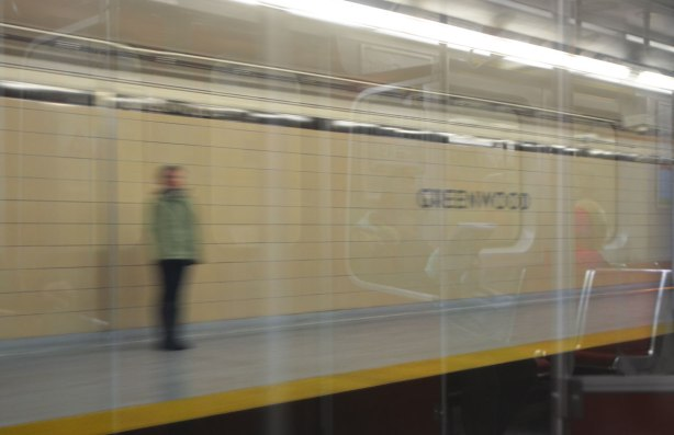 blurry person standing on the platform at Greenwood station, with reflections of people sitting on the subway