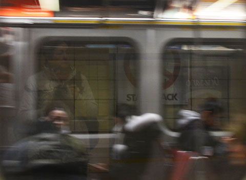 reflections in the subway window along with people sitting on the train