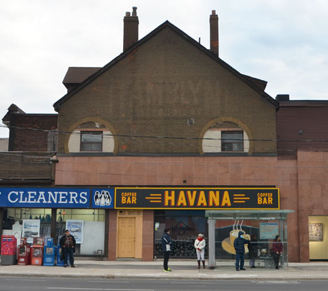 old building with ghost sign on the upper storey, Tamblyns, bottom part now a dry cleaners and the Havana bar and grill.  A bus shelter is beside the building and some people are waiting for a bus.