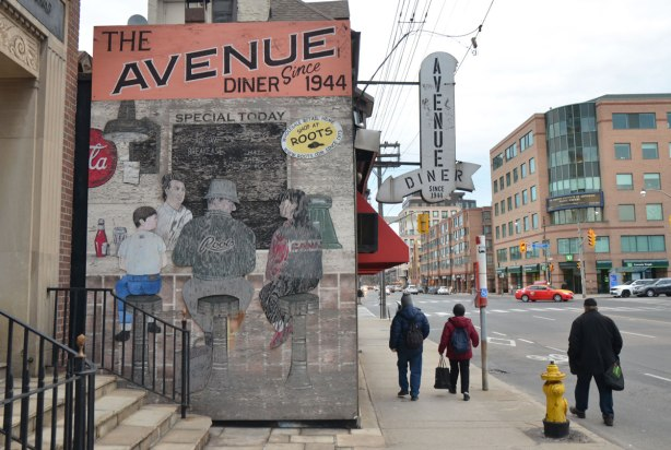 old faded mural painted on wood on the exterior side wall of the Avenue Diner. shows people sitting at a lunch counter with an employee behind
