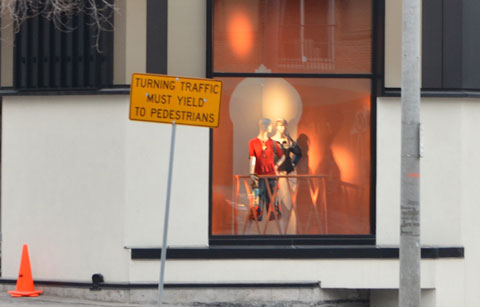 a yellow traffic sign in front of a store window. Window is lit and has two female mannequins in it. Sign says Turning traffic must yield to pedestrians.