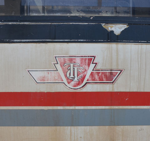 faded TTC symbol on the exterior of a rapid transit vehicle