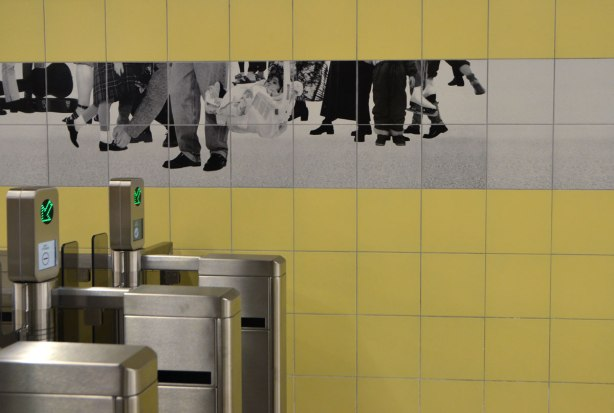 photos of peoples legs and feet in black and white on tiles on a yellow tiled subway station wall, over the metal turnstiles for entry into the station, artwork by Sylvie Belanger