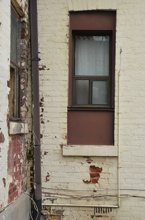two windows with brown frames on a cream coloured wall with the paint peeling to reveal the red brick beneath