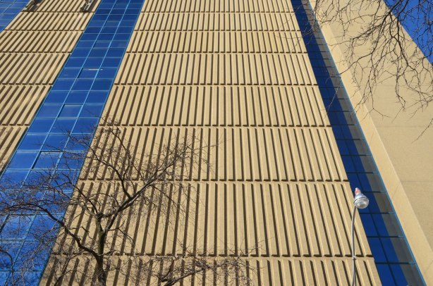looking up a building with strong vertical lines made by concrete shapes on theglass is reflecting strong blue colour exterior of the building,