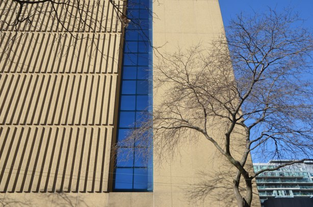 looking up a building with strong vertical lines made by concrete shapes on theglass is reflecting strong blue colour