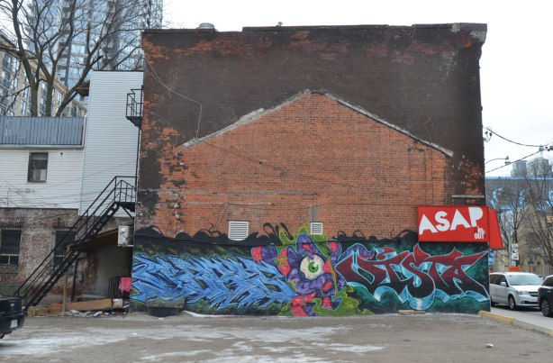 a mural across the bottom of a red brick building, beside a parking lot, eyeball in the middle, a tag on either side, the one on the right is probably vista