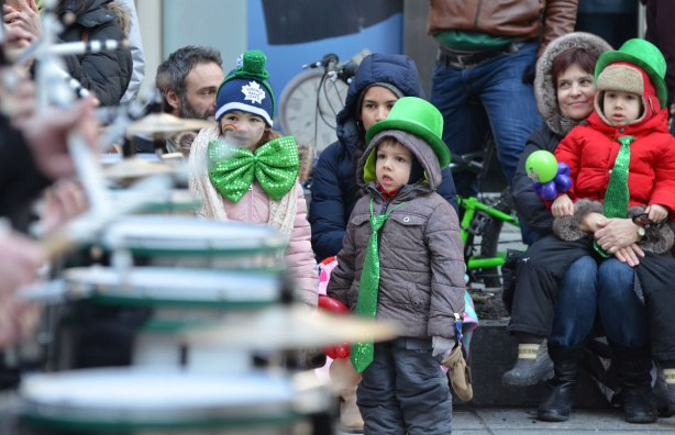 adults and kids sitting on the sidewalk watch drummers go past in a parade. girl with big green bowtie and boy with long green tie and green bowler hat