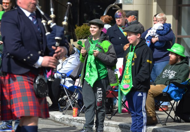 two boys wearing hats and oversized green ties watch a band march past in the St. Patricks day parade, bag piper in the very foreground.