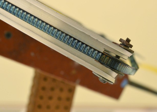 close up of a sculpture of an automatic rifle where the round of ammo is replaced by a reel of film