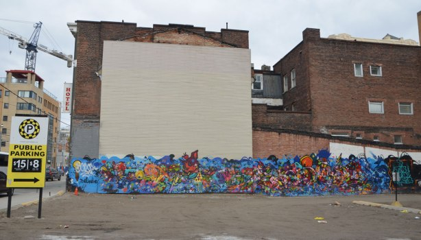 a long horizontal mural across the bottom of two buildings beside a parking lot in downtown Toronto, the Dream Chaser