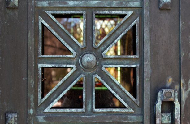 close up of a pane in a window with a metal window frame, square with lines dividing the pane into 8 triangles, stained glass window in the background. Looking into a vault at a cemetery