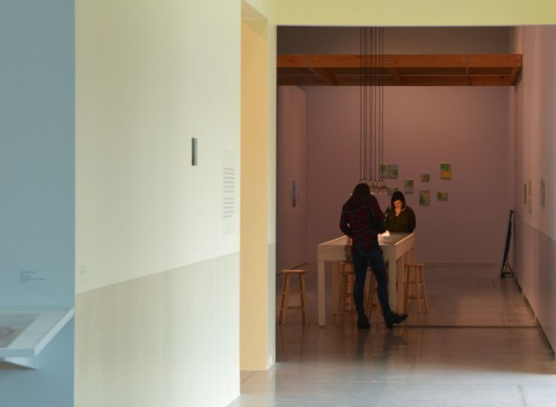 two women looking over a table with art displays on it , in an art gallery