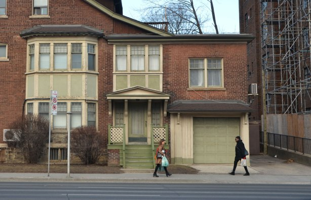 two women walk past a brick house with green wood features, porch, windows, garage door.