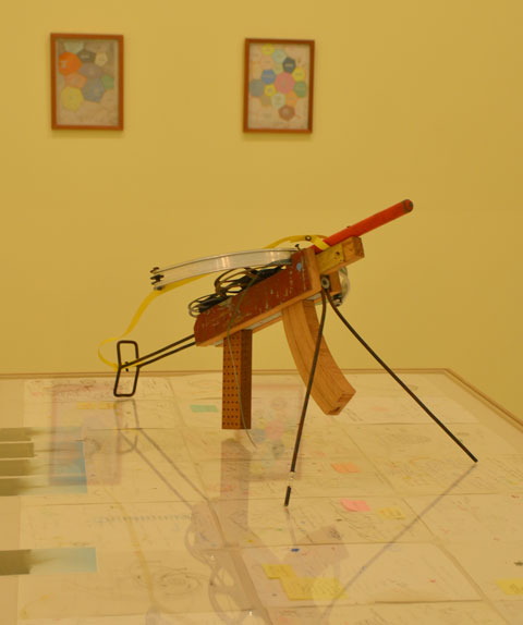 in a yellow room with two small pictures hanging crookedly on the wall. A table in the middle of the room, glass covering artwork on the table. Sitting on the table is an automatic rifle (artwork) made of found objects
