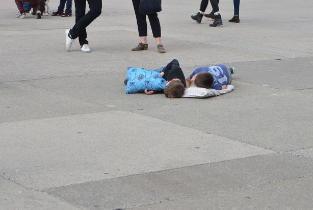 two boys lie on pillos on the concrete ground of Nathan Phillips Square