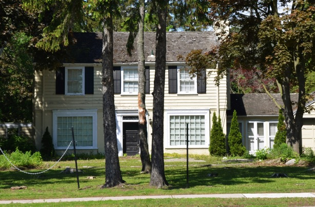 older two storey house, pale yellow, with black and white trim and black front door, mature trees in the front yard.