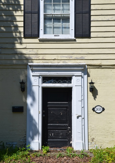 front door of an older house, number 2450, pale yellow walls, white frames around door and window, black door, black shutters,