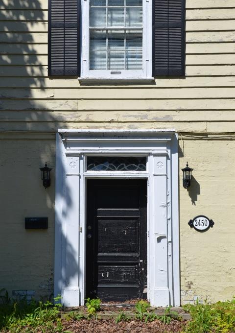 front door of an older house, number 2450, pale yellow walls, white frames around door and window, black door, black shutters,