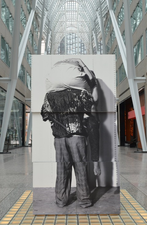 photographs of the back of a person with another person sitting on his shoulders, upper person is leaning forward with head down, the blocks on which the photos are printed are in the walkway at Brookfield Place