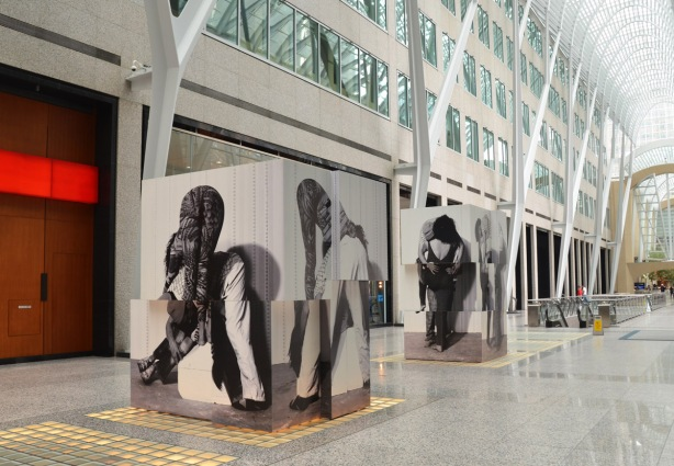 two large cubes constructed from pieces of photos of different people in different positions sit in the middle of Brookfield Place, under the glass arched roof.