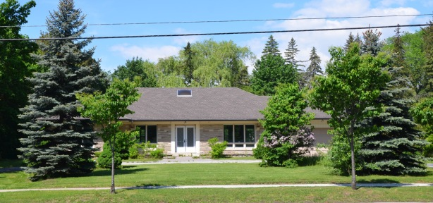 large bungalow set back from the street behind a few pine trees, brown roof, stone facing on the exterior, large lawn,