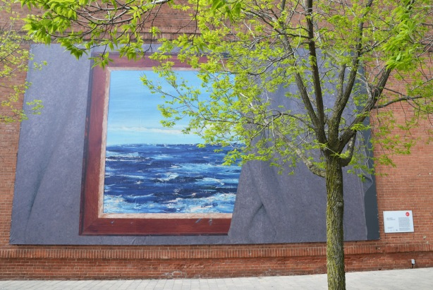 a large art installation on the south exterior wall of the Power Plant contemporary art gallery, with a small tree in front of it.