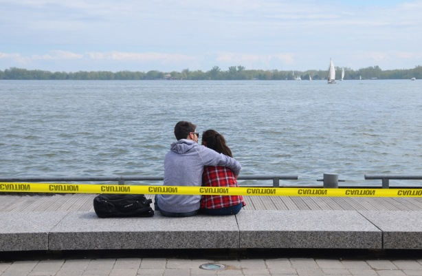 a young couple sits by the waterfront, on a stone bench. He has his arm around her. There is yellow caution tape behind them because the water level in Lake Ontario is high.