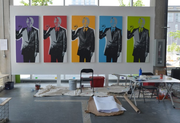 indoor temporary gallery for the Making Peace exhibit, a painter is in the midst of creating a large painting of five copies of a picture of Nelson Mandela, each copy is in a different colour, purple, red, orange, blue and green,