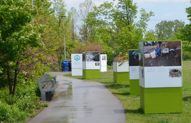 outdoor exhibit, Corktown Commons, short pillars with 4 sides, each side has a picture and a description, the background colour is green which represents the environment and sustainability.