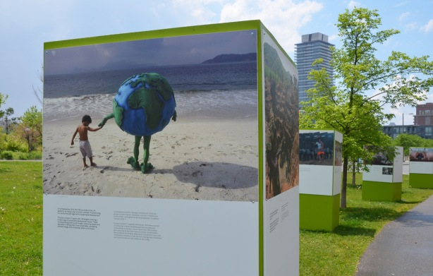 a photo of a person dressed in a large blue and green Planet Earth costume, holding the hand of a young boy as the walk on a beach towards the water