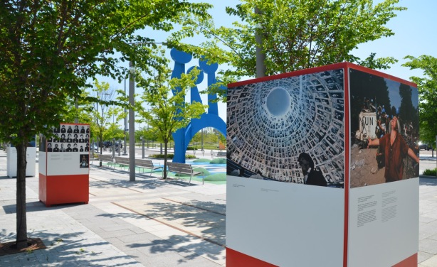 an outdoor art exhibit on peace, two of the structures used for mounting pictures on, with the blue sculpture on Front Street, Canaray District, in between the two boxes.