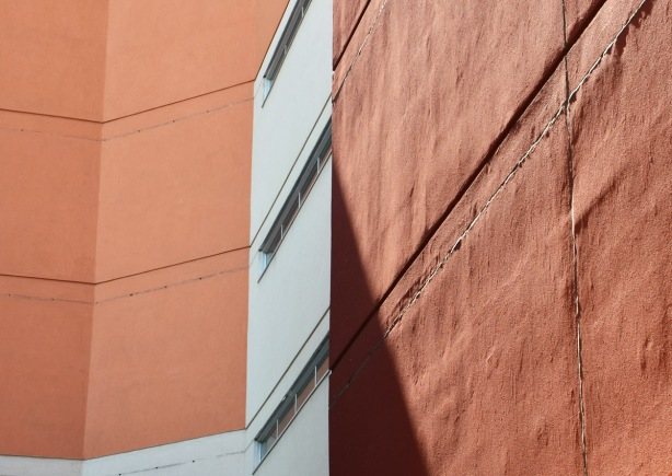 on an angle, rusty brown coloured wall with horizontal windows on a white section