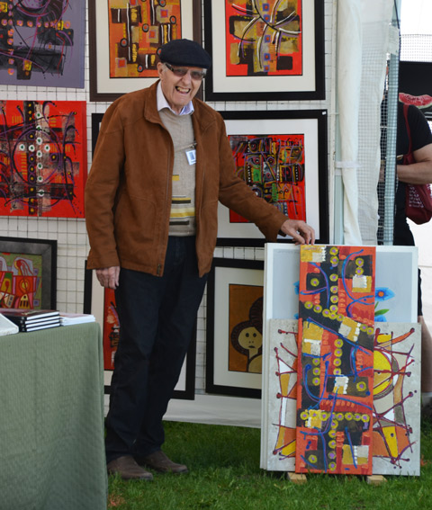 a man stands holding up a painting (bottom of painting is resting on the ground), more painting displayed on the wall behind him, at the outdoor Riverdale Artwalk art show and sale