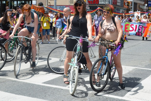 dykes on bikes stop in the parade for a photo op. one woman is topless with a bicycle painted on her chest.