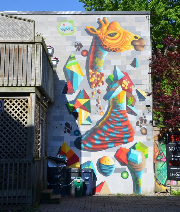 a tall mural by birdo of a giraffe in many pieces, a yellow and orange head, a blue and red body and a number of multicoloured legs