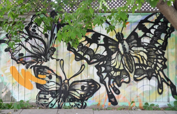 Three black line drawings of a butterfly, with details and shadowing, very realistic looking, on a fence