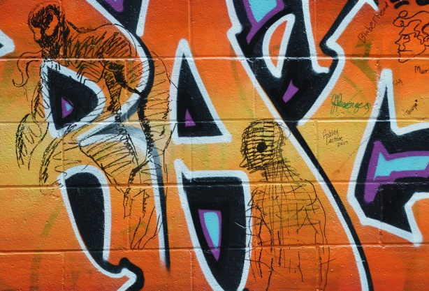 two figures, drawn abstractly with black marker on top of orange street art,