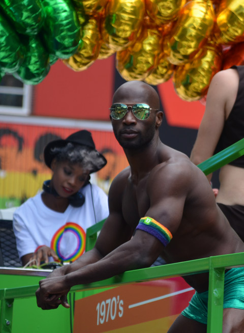a black man wearing just green tight shorts and green sunglasses is standing on the TD float, a woman is in the background (she is looking after the music).