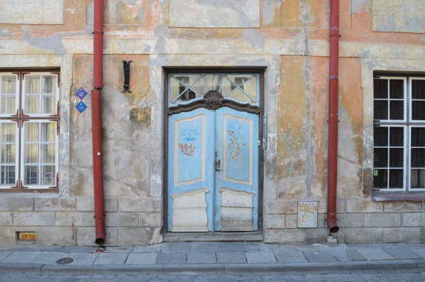 front door of a house in Tallinn Estonia, wood, blue and white double doors, orange faded paint on the concrete facade, 2 red drain pipes run down the front, one on each side of the door