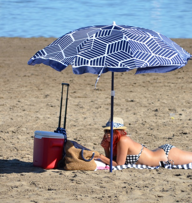 a woman with red hair lies under a blue and white umbrella on the beach by Lake Ontario
