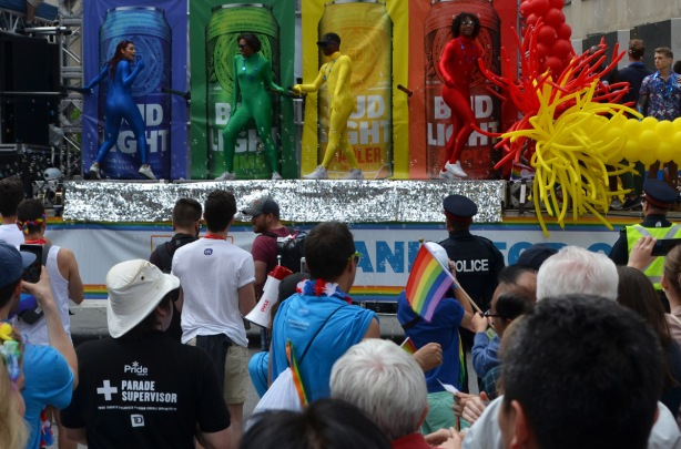bud light float at pride, picture of 4 large cans - a blue, green, red, and yellow can with a person in front of each in a tight body suit the same colour as the can. crowd in front of the float.