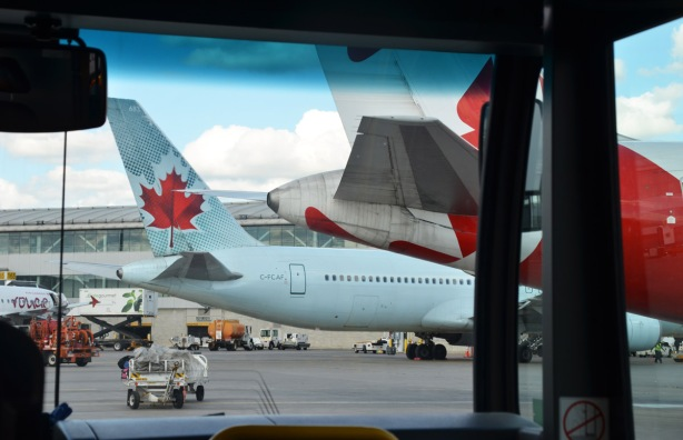 looking through the front window of a bus as it drives on the tarmac behind aiplanes parked at gates