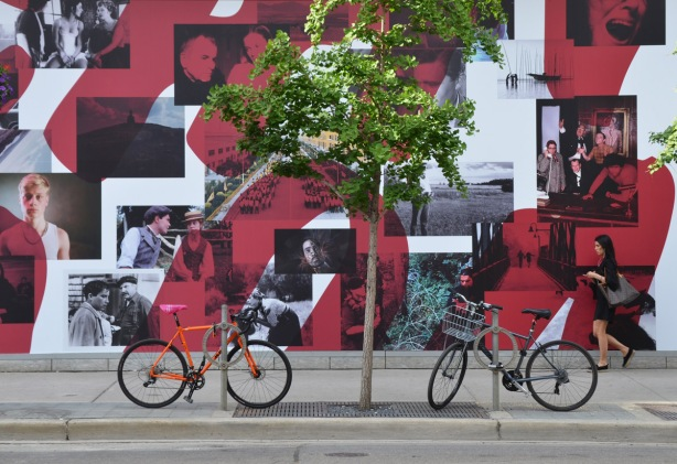 bikes parked in front of a large poster advertising TIFF's Canada on Screen program, a collage of black and white pictures taken from movies.