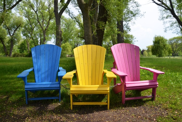 three muskoka chairs sitting in a line, a blue, yellow and pink chair. trees and grass behind them