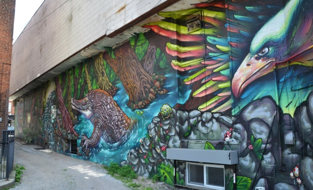 part of a large colourful mural by clandestinos smoky and shalak - bird, turtle and croodile in a nature scene