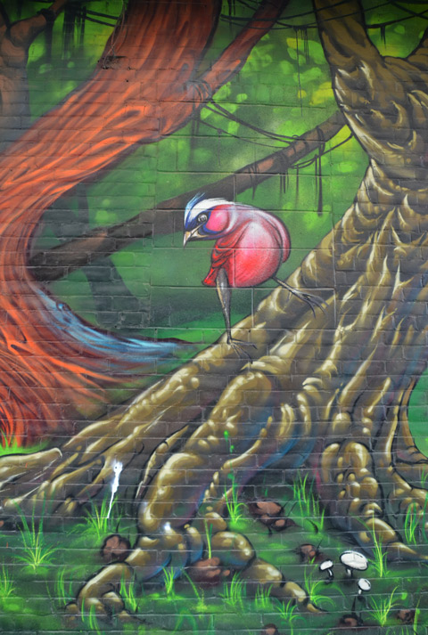 part of a large colourful mural by clandestinos smoky and shalak - a small bird on the base of a tree trunk