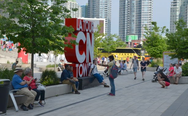 3D sign for the CN tower with tourists taking pictures in front of it. Canada 150 3D sign in the background as well as some people sitting around on benches