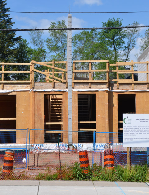 from the front, street view, two of a row of townhouses under construction, plywood exterior with holes where the doors and windows are going to be.