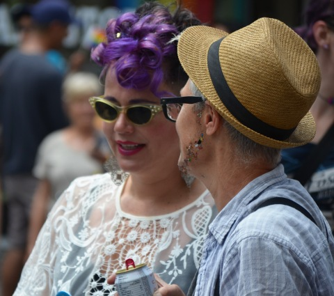 a couple - one is a purple wig and sunglasses and the other in a straw hat with sparkles glued to her face in the shape of a thin beard